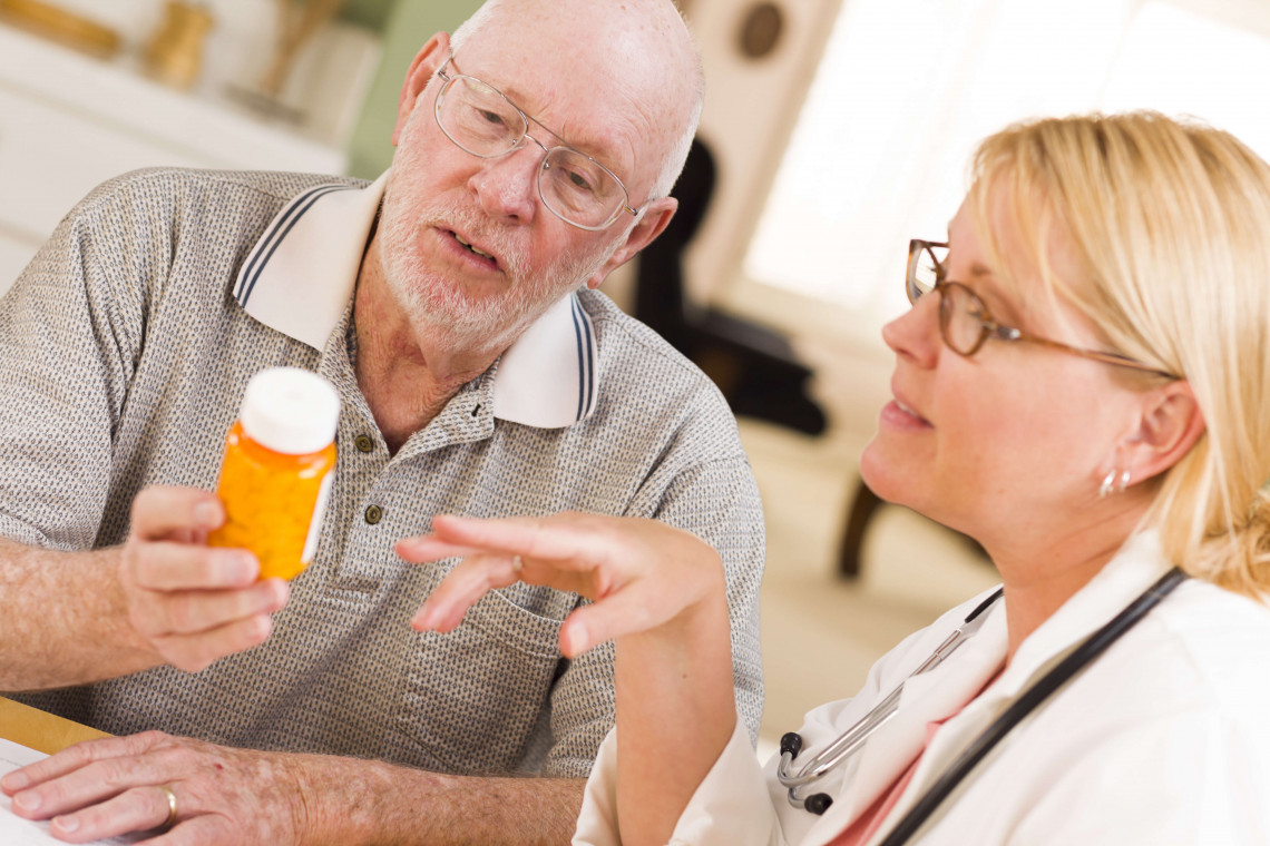 Doctor or Nurse Explaining Prescription Medicine to Attentive Senior Man.
